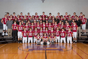 Coaches and football team posing for a photo