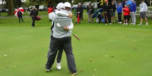 Two golf players hugging during a game