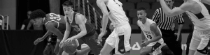 Black and white image of basketball players during a game