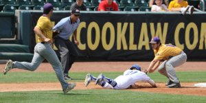 Baseball players running to block the opposing team from sliding into base