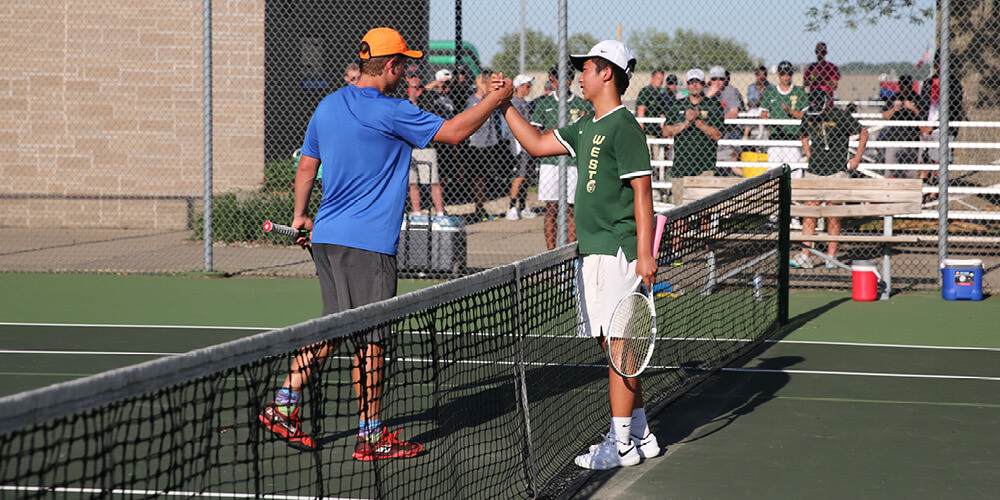 Two players shake hands over the net during a tennis match