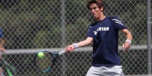 Xavier tennis player hitting the ball mid air