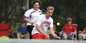 Tennis player hitting the ball mid air