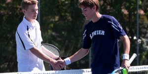 Two tennis players shaking hands across the net