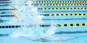 Swimmers splash into the water during a meet