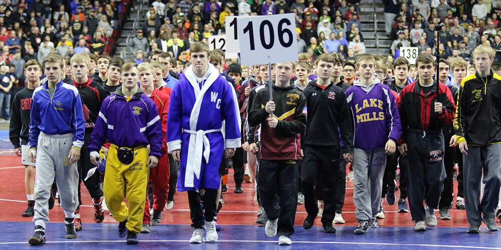 Image of students holding up a sign with the number 106 during a wrestling match